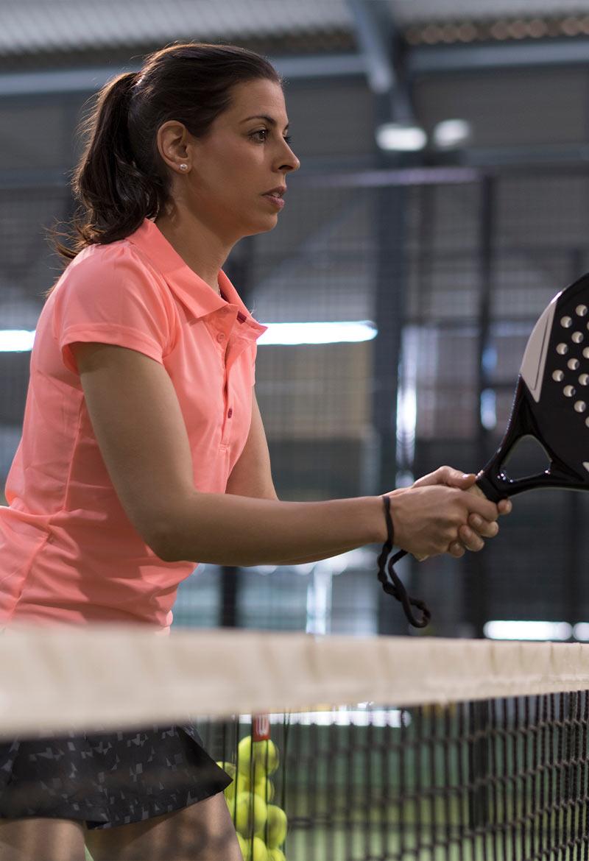 Mujer en la red de la pista de padel